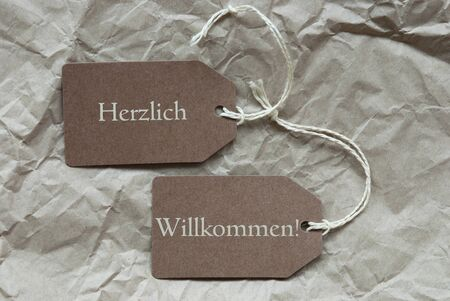 willkommen: Two Brown Labels Or Tags With White Ribbon On Crumpled Paper Background With German Text Herzich Willkommen Means Welcome Vintage Or Retro Style