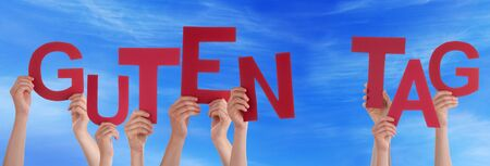 guten tag: Many Caucasian People And Hands Holding Red Letters Or Characters Building The German Word Guten Tag Which Means Good Day On Blue Sky