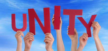 unify: Many Caucasian People And Hands Holding Red Letters Or Characters Building The English Word Unity On Blue Sky