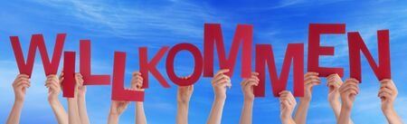 willkommen: Many Caucasian People And Hands Holding Red Letters Or Characters Building The German Word Willkommen Which Means Welcome On Blue Sky
