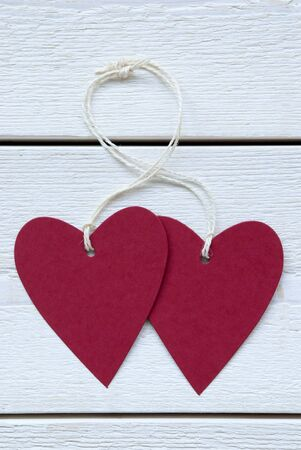 Vertical Image With Two Empty Red Hearts Label With White Ribbon On White Wooden Background photo