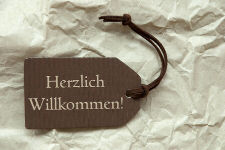 willkommen: One Brown Label Or Tag With Brown Ribbon On Crumpled Paper Background With German Text Herzlich Willkommen Means Welcome Vintage Or Retro Style