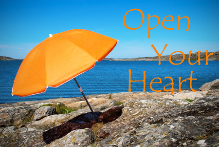 open your heart: Beach With Orange Parasol And English Life Quote Open Your Heart With Ocean And Open Sea Sunny Weather With Blue Sky Stock Photo
