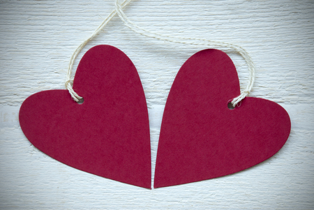 Two Empty Red Hearts Label Or Tag With White Ribbon On White Wooden Background photo