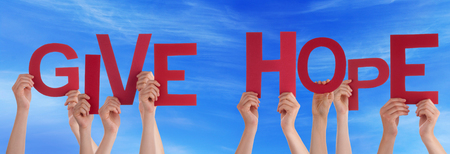hope: Many Caucasian People And Hands Holding Red Letters Or Characters Building The English Word Give Hope On Blue Sky Stock Photo