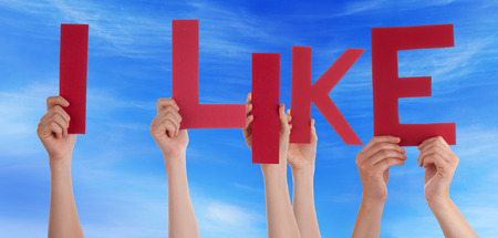 like english: Many Caucasian People And Hands Holding Red Letters Or Characters Building The English Word I Like On Blue Sky Stock Photo