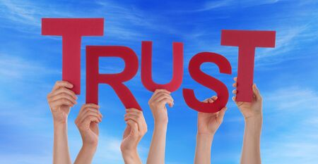 trust people: Many Caucasian People And Hands Holding Red Letters Or Characters Building The English Word Trust On Blue Sky Stock Photo