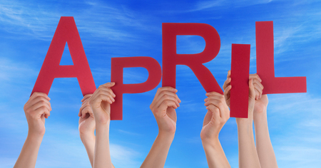 Many Caucasian People And Hands Holding Red Letters Or Characters Building The English Word April On Blue Sky photo