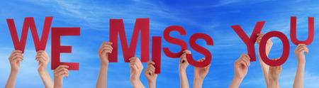 Veel blanke mensen en handen die rode letters of tekens bouwen van het Engels woord We missen je Op Blauwe Hemel