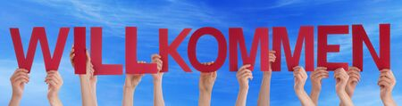 willkommen: Many Caucasian People And Hands Holding Red Straight Letters Or Characters Building The German Word Willkommen Which Means Welcome On Blue Sky