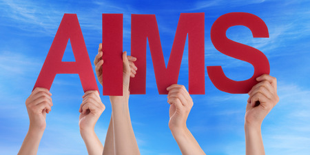 aims: Many Caucasian People And Hands Holding Red Straight Letters Or Characters Building The English Word Aims On Blue Sky