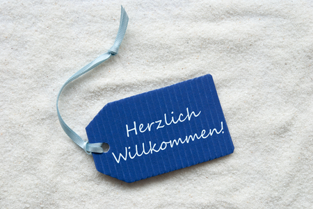 willkommen: One Blue Label Or Tag With Light Blue Ribbon On White Sand Background With German Text Herzlich Willkommen Which Means Welcome
