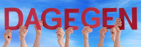 dislike it: Many Caucasian People And Hands Holding Red Straight Letters Or Characters Building The German Word Dagegen Which Means Against It On Blue Sky Stock Photo