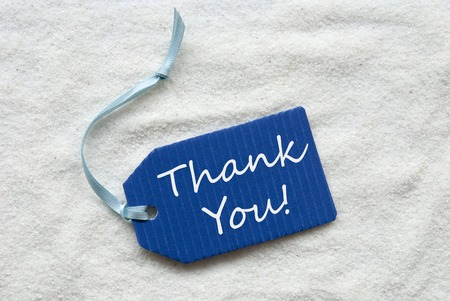 One Blue Label Or Tag With Light Blue Ribbon On White Sand Background With English Text Thank You
