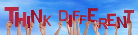 think different: Many Caucasian People And Hands Holding Red Letters Or Characters Building The English Word Think Different On Blue Sky