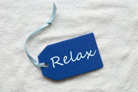 downtime: One Blue Label Or Tag With Light Blue Ribbon On White Sand Background With English Text Relax