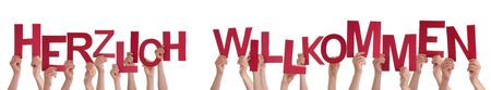 willkommen: Many Caucasian People And Hands Holding Red Letters Or Characters Building The Isolated German Word Herzlich Willkommen Which Means Welcome On White Background Stock Photo