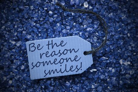 small stones: One Blue Label Or Tag With Black Ribbon On Blue And Purple Small Stones As Background. English Life Quote Be The Reason Someone Smiles With Frame