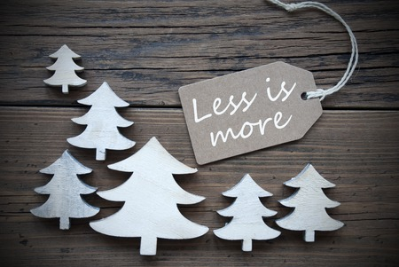 frame less: Brown Christmas Label With Ribbon On Wooden  Background With White Christmas Trees. Vintage Style. Label With English Quote Less Is More For Christmas Or Season Greetings