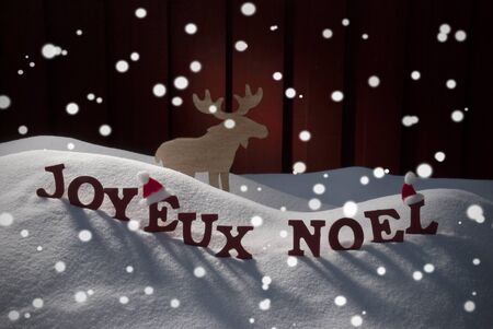 christmas atmosphere: Red Letters Building French Word Joyeux Noel Means Merry Christmas As Decoration Card. Snow And Snowy Scenery With Snowflakes Moose And Santa Hat. Wooden Background. Christmas Atmosphere Stock Photo