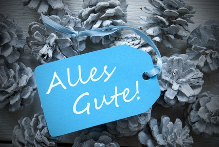 best wishes: One Light Blue Label On Fir Cones And White Wooden Background. German Text Alles Gute Means Best Wishes Vintage Or Retro Style Used As Winter Or Christmas Background With Frame Stock Photo