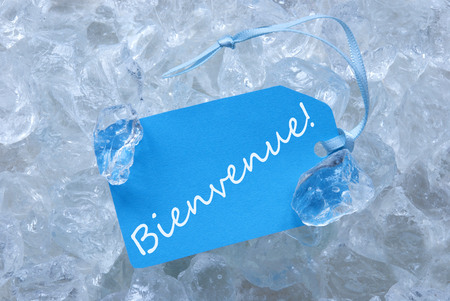 french text: Light Blue Label With Blue Ribbon On White Transparent Curshed Ice Cubes As Background. French Text Bienvenue Means Welcome For Cool Greetings.Close Up Or Macro View.