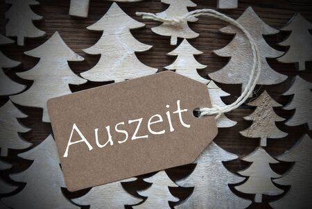 auszeit: Brown Christmas Label With Ribbon On Wooden Christmas Trees Background. Vintage Style. Label With German Text Auszeit  Means Downtime For Christmas Or Season Greetings.Close Up Or Macro