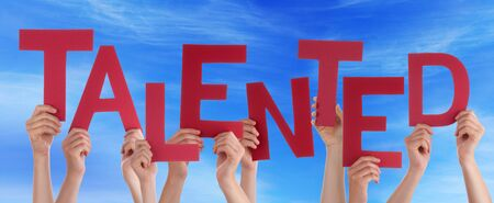 talented: Many Caucasian People And Hands Holding Red Letters Or Characters Building The English Word Talented On Blue Sky Stock Photo