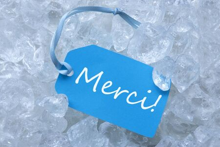 icecubes: Light Blue Label With Blue Ribbon On White Transparent Curshed Ice Cubes As Background. French Text Merci Means Thank You For Cool Greetings.Close Up Or Macro View. Stock Photo