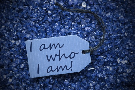 i am: One Blue Label Or Tag With Black Ribbon On Blue And Purple Small Stones. Background With English Life Quote I Am Who I Am With Frame