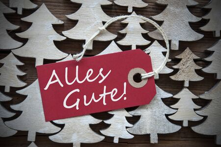 best wishes: Red Christmas Label With Ribbon On Wooden Christmas Trees Background. Vintage Or Rustic Style. Label With German Text Alles Gute Means Best Wishes For Christmas Or Season Greetings.Close Up Or Macro