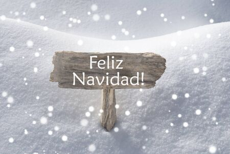 christmas atmosphere: Wooden Christmas Sign With Snow In Snowy Scenery. Spanish Text Feliz Navidad Means Merry Christmas For Seasons Greetings Or Christmas Greetings. Christmas Atmosphere With Snowflakes