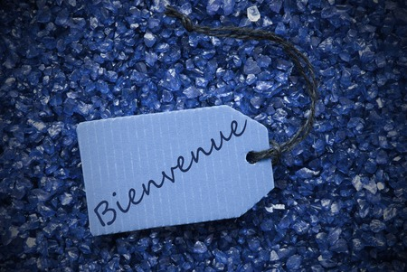french text: One Blue Label Or Tag With Black Ribbon On Blue And Purple Small Stones As Background With French Text Bienvenue Means Welcome With Frame