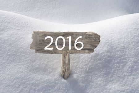 christmas atmosphere: Wooden Christmas Sign With Snow In Snowy Scenery. English Text 2016 For Seasons Greetings Or Happy New Year Greetings. Christmas Atmosphere.