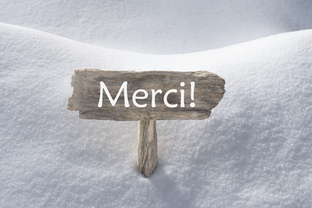 french text: Wooden Christmas Sign With Snow In Snowy Scenery. French Text Merci Means Thank You For Seasons Greetings Or Christmas Greetings. Christmas Atmosphere.