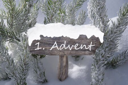 free image: Wooden Christmas Sign With Snow And Fir Tree Branch In The Snowy Forest. German Text 1 Advent Means Christmas Time For Seasons Greetings Or Christmas Greetings. Christmas Atmosphere.