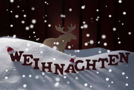 christmas atmosphere: Red Letters Building German Word Weihnachten Means Christmas.Decoration Card For Seasons Greetings. Snow And Snowy Scenery With Snowflakes Moose And Santa Hat. Wooden Background. Christmas Atmosphere