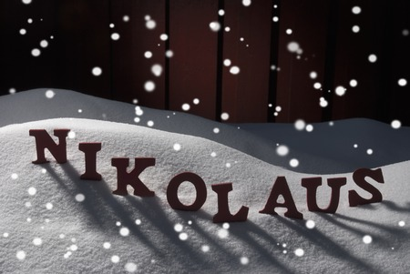 nikolaus: Red Wooden Letters Building German Word Nikolaus Means Santa Claus. Christmas Decoration Or Christmas Card. Snow And Snowy Scenery With Snowflakes In Front Of Wooden Background. Christmas Atmosphere Stock Photo