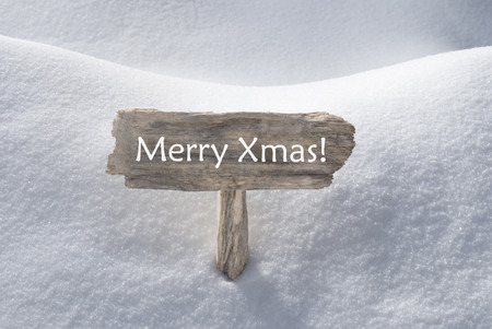 Wooden Christmas Sign With Snow In Snowy Scenery. English Text Merry Xmas For Seasons Greetings Or Christmas Greetings. Christmas Atmosphere.