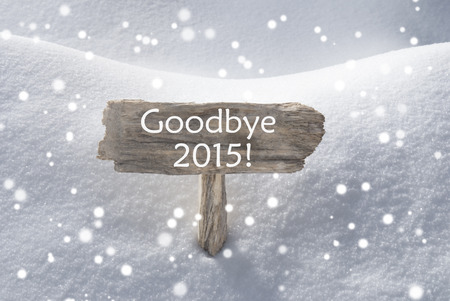 christmas atmosphere: Wooden Christmas Sign With Snow In Snowy Scenery. English Text Goodbye 2015 For Seasons Greetings Or Christmas Greetings Or Happy New Year Greetings. Christmas Atmosphere With Snowflakes Stock Photo