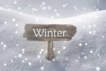 christmas atmosphere: Wooden Christmas Sign With Snow In Snowy Scenery. English Text Winter For Seasons Greetings Or Christmas Greetings. Christmas Atmosphere With Snowflakes