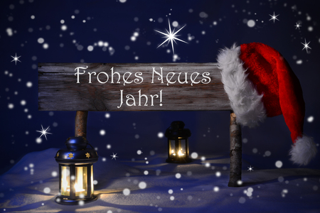 jahr: Wooden Christmas Sign And Santa Hat With Snow. German Text Frohes Neues Jahr Means Happy New Year For Seasons Greetings. Blue Silent Night With Snowflakes And Sparkling Stars. Lantern And Candlelight