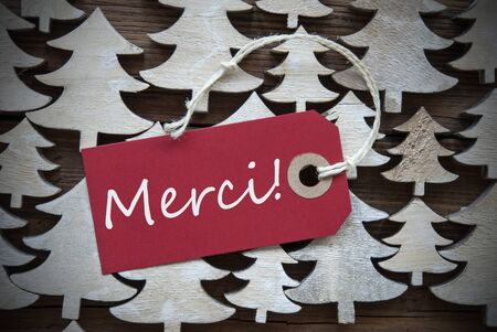 french text: Red Christmas Label With Ribbon On Wooden Christmas Trees Background. Vintage Or Rustic Style. Label With French Text Merci Means Thank You For Christmas Or Season Greetings.Close Up Or Macro Stock Photo