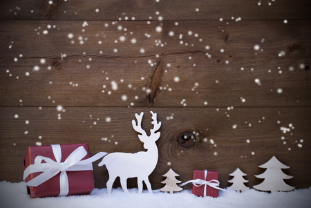 season greetings: Christmas Decoration With Red Gifts Or Presents Moose Or Reindeer And Christmas Trees On Snow. Card For Seasons Greetings. Copy Space For Advertisement. Snowflakes Infront Wooden Background