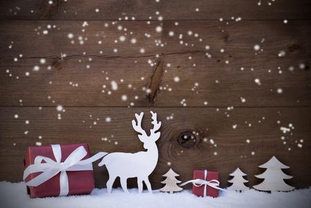 Weihnachtsschmuck mit roten Geschenke oder Geschenke Elch oder Rentier und Weihnachtsbäume auf Schnee. Karte für Seasons Greetings. Kopieren Sie Platz für Werbung. Schneeflocken Infront Wooden Background
