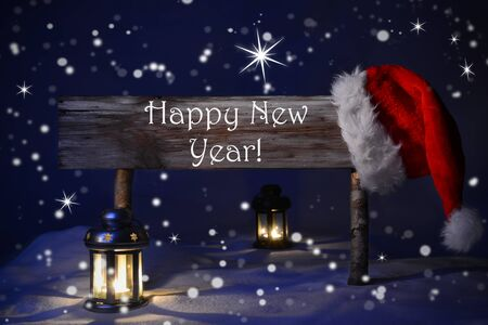 text year: Wooden Christmas Sign And Santa Hat With Snow In Snowy Scenery. English Text Happy New Year For Seasons Greetings. Blue Silent Night With Snowflakes And Sparkling Stars. Lantern And Candlelight Stock Photo