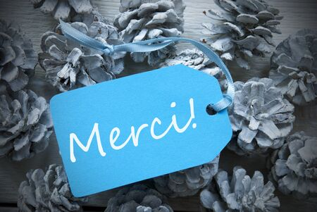 french text: One Light Blue Label On Fir Cones And White Wooden Background. French Text Merci Means Thank You Vintage Or Retro Style Used As Winter Or Christmas Background With Frame