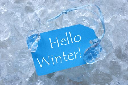 icecubes: Light Blue Label With Blue Ribbon On White Transparent Curshed Ice Cubes As Background. English Text Hello Winter For Cool Greetings.Close Up Or Macro View. Stock Photo