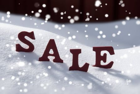 christmas atmosphere: Red Wooden Letters Building Red Word Sale In Christmas Time Or Season Snow And Snowy Scenery With Snowflakes In Front Of Red Wooden Background. Christmas Atmosphere