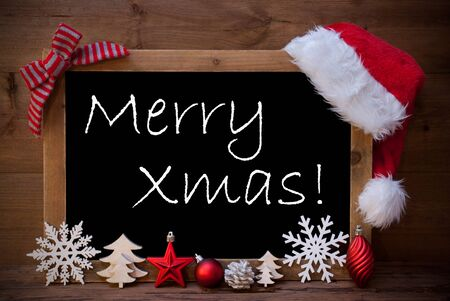 like english: Blackboard With Red Santa Hat And Christmas Decoration like Snowflake, Tree, Christmas Ball, Fir Cone, Star. English Text Merry Xmas. Brown Wooden Background Stock Photo